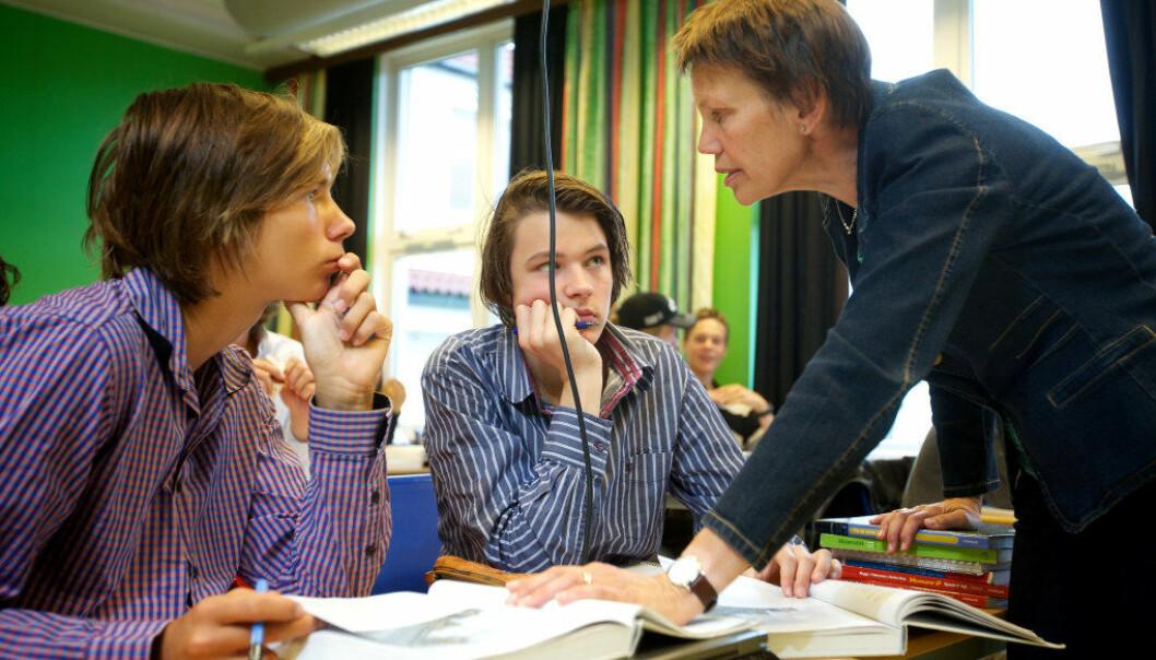 Norsklærer Lisbeth Norendal forklarer hva elevene Sondre Fossmark og Mats Hop Andersen ved Fana gymnas skal arbeid med. (Foto: Bjørn Erik Larsen)