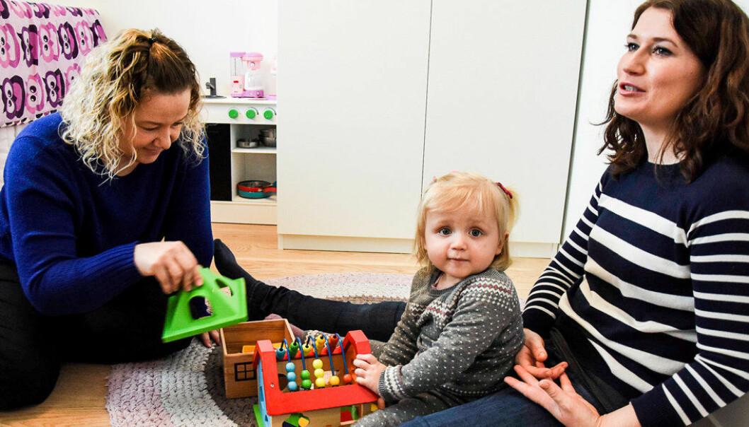 Barnehageansatt Anita O'Bray nærmer seg Julie (1) forsiktig hjemme på barnerommet hennes før barnehagestart i iFokus Lysheim barnehage i Larvik, mens Julie ennå er trygg på mamma Anne Lines fang. Foto:Sigrid Ringnes