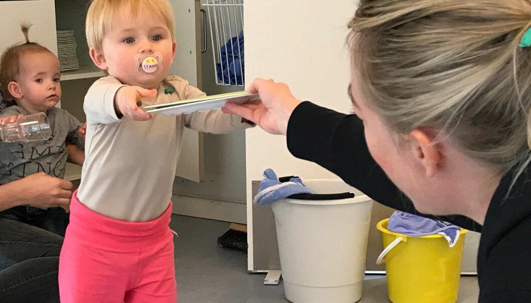 Barna i Rørsangervej barnehage hjelper til med å dekke bordet i overgangen fra lek til måltidet. Barnehagen flyttet tallerkener og bestikk i barnehøyde, slik at Thea og Anine lett kan hjelpe pedagogisk medhjelper Anne Smith (t.h.) med å dekke bordet. Foto: Miriam Lykke Schultz