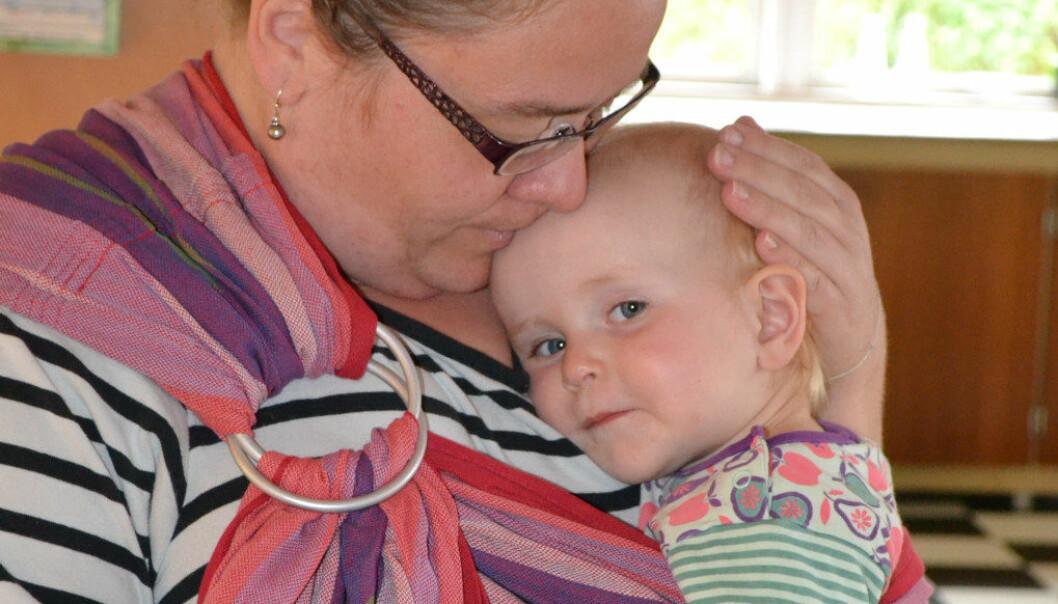 Pedagog Pia Rønver i Stenstrup barnehage i Danmark opplever at barn som Alva får dekket behovet sitt for nærhet i bæreslyngene. Foto: Britta Napier