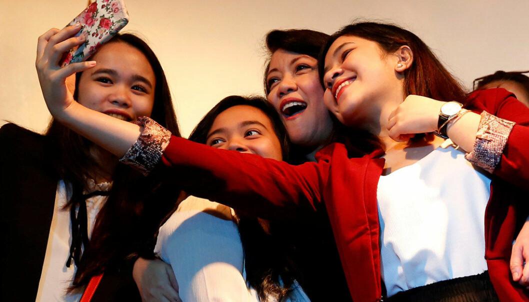 Filippinenes høyesterettsdommer Maria Lourdes Sereno poserer med studenter fra en katolsk skole. Sereno tok til orde for kvinners rettigheter på kvinnedagen. Foto: AP / NTB scanpix