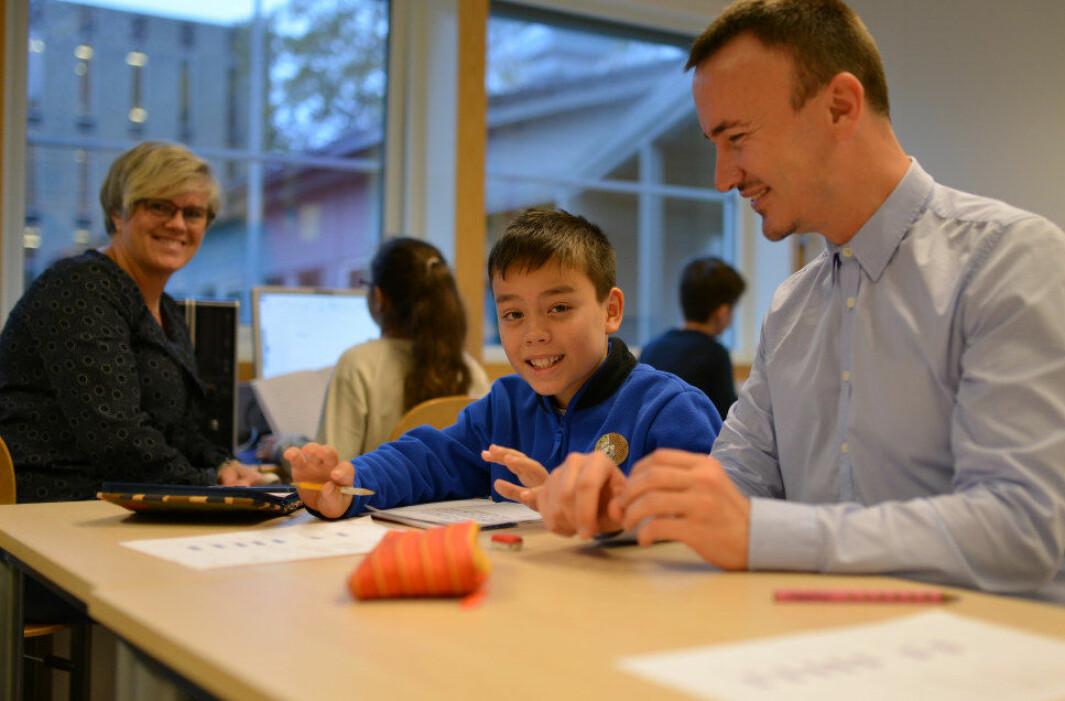 Elevene i fjerde klasse får hjelp til leksene. Fra v.: Inger Bente Løvfall, William Bjørnstad (10) og rektor Kjartan Navarsete. Foto: Wenche Schjønberg