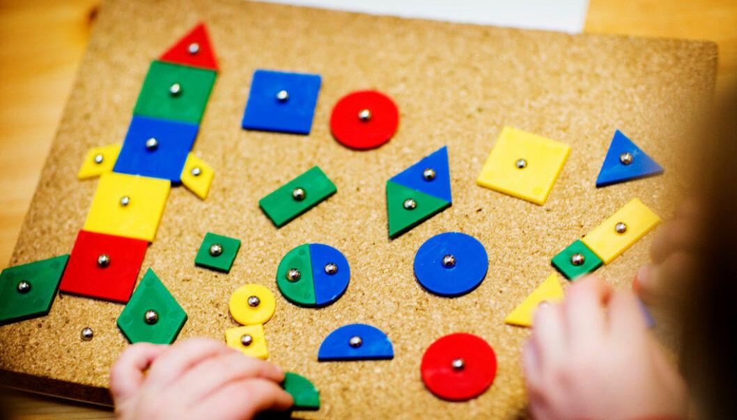 Flate former i rødt, grønt, blått og gult plasseres på korkunderlag og er banket fast med stift. Spikerspillet gir anledning til å øve på geometriske former. Nå viser en undersøkelse at matematikk blir en større og større del av læringen til barnehagebarn. Arkivfoto: Utdanning