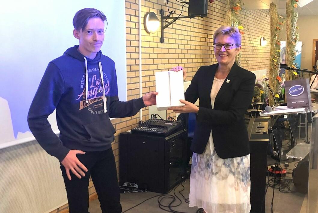 Rektor Anne Johanne Guldvik overrekker en iPad til Vetle S. Bjurstrøm etter at han kom seg gjennom skoleåret uten fravær. Foto: Hans Skjong