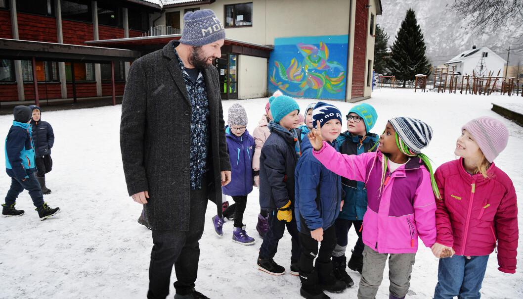 Rektor Bjarte Ramstad snakker litt om det å ha venner med førsteklassingene som skal på tur. På hodet har han tatt på seg lue med påskriften «mot mobbing». Foto: Oddrun Midtbø
