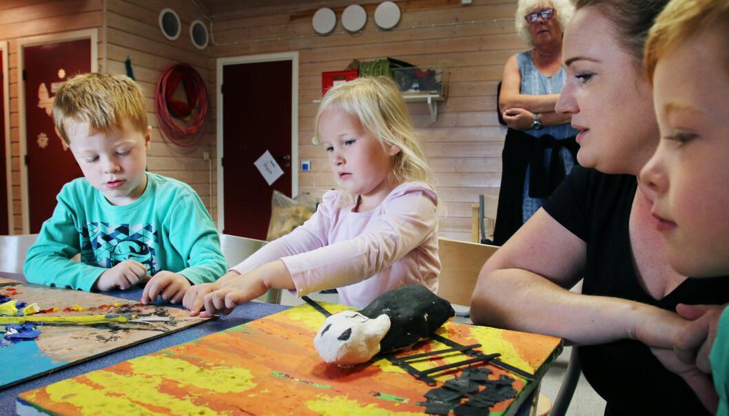Edvard, Malin og Aksel ser og kjenner på malerier barna har laget inspirert av Munch. Sammen med dem sitter pedagogisk leder Linda Orskaug, og i bakgrunnen står pedagogisk leder Marit Bø Johannessen. Foto: Jørgen Jelstad