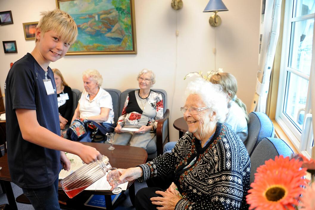 Phillip Gustavsen skjenker saft til Grethe Stornes.  I bakgrunnen ser vi Signe H. Johnsen og Astrid K. Halvorsen. Foto: Marianne Otterdahl-Jensen