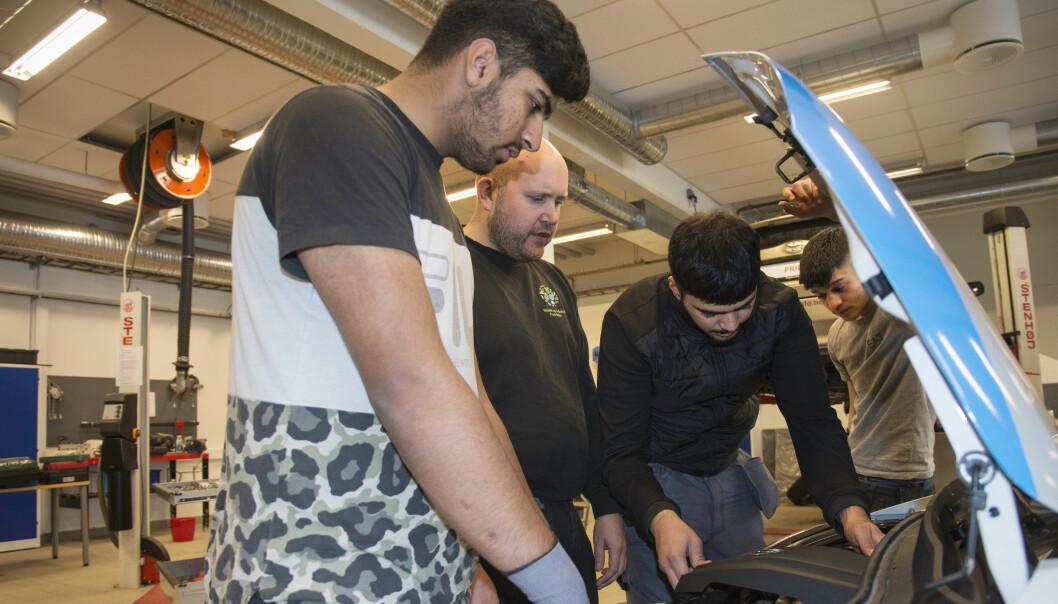 Det er mye som er forskjellig fra en elbil til kjøretøy som går på bensin eller diesel, og elevene får en innføring. Det er fra venstre Faiz Alam, kontaktlærer Arnfinn Gilberg, Danish Khan og Saqlain Haroon.