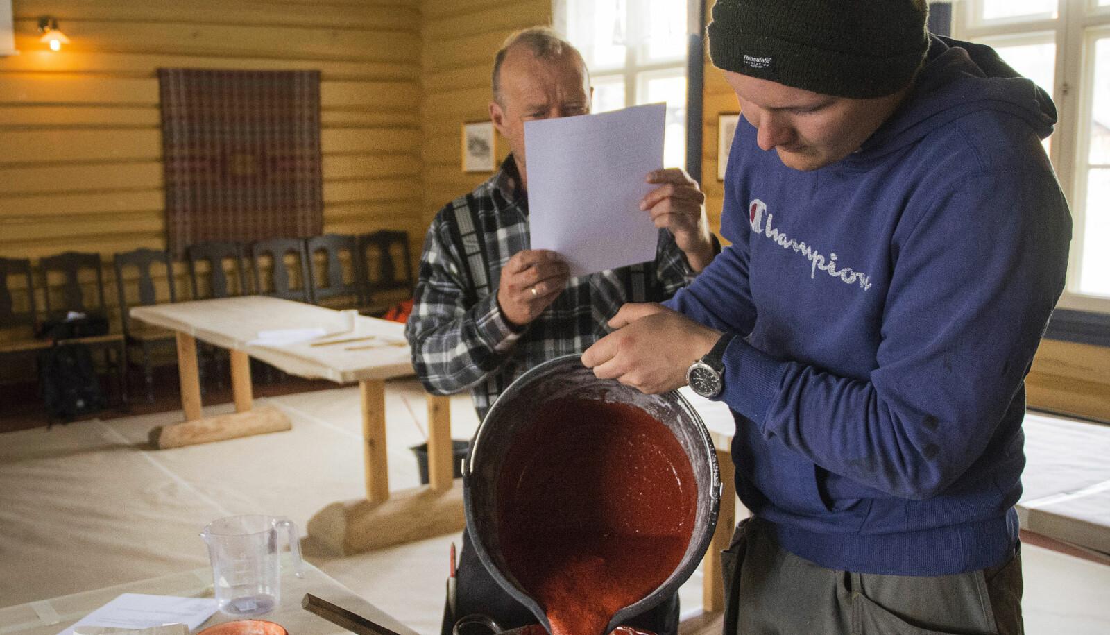 Studentene må lage malingen de skal bruke selv. Her er det Håkon Martinsen som tømmer komposisjonsmaling, mens Knut Gunnar Martinsen leser oppskriften.