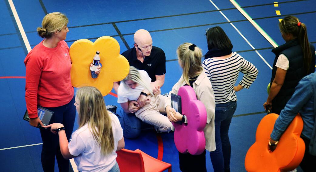 Børge Stave viser et par holdeteknikker til en av lærerne i en pause.