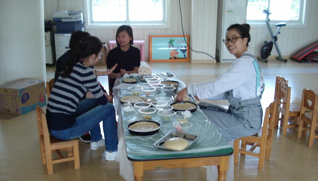 Lærer miss Zhou (t.h.) er på planleggingsmøte sammen med andre lærere i barnehagen. De lager pizza og diskuterer hvordan de skal gjennomføre pizzabaking i klassen neste uke.