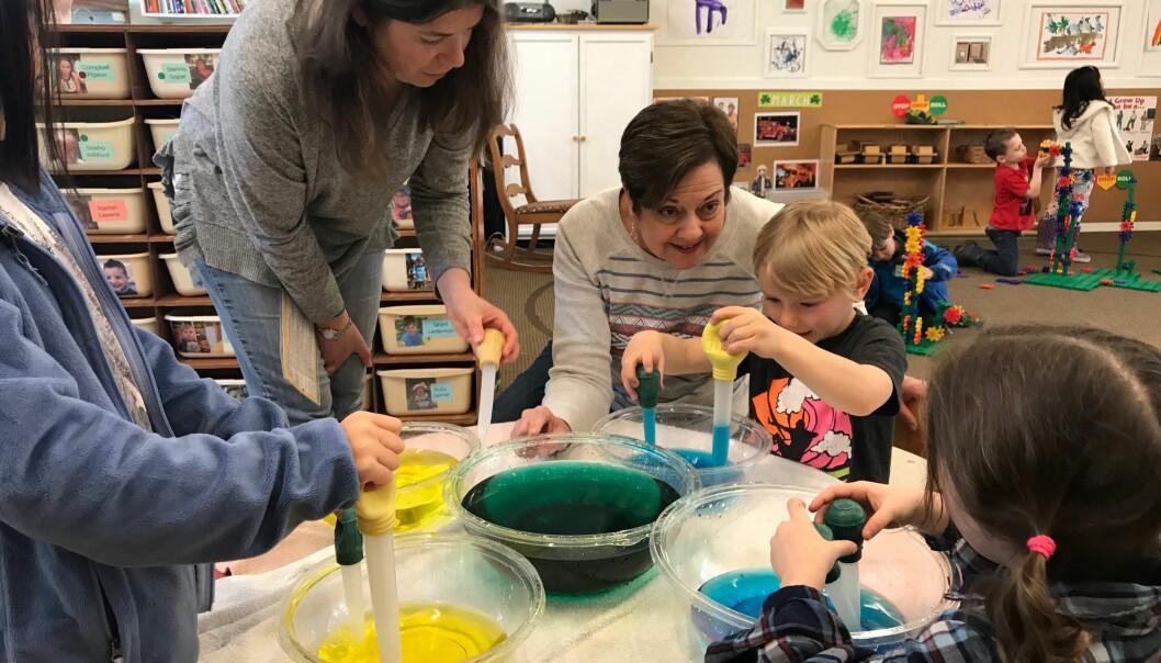Barnehagelærer Connie Hawkins (midten) sier hun er blitt en bedre pedagog ved å jobbe sammen med foreldre, fordi de forventer det beste av henne hver dag. Her hjelper de barna Wes og Mylie med å se hva som skjer når de blander fargene blått og gult.