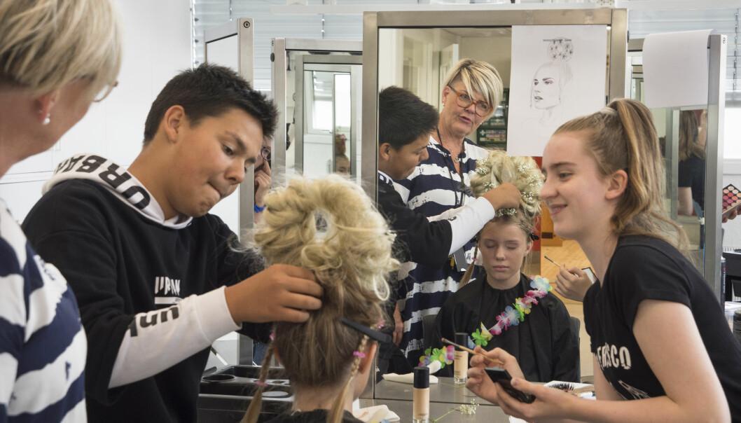 Kevin Sharma og Viktoria Nordlien Tallerås er i sving for å fikse frisyren til Kamilla Haukås. Faglærer Eva Enderud Larsen følger med.