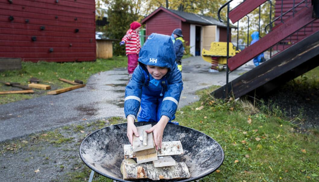 Eilif (5) fyller opp bålpanna. Barn opparbeider motorikk og kognitiv evne til å vurdere egne grenser gjennom lek ispedd risiko. Slik er risikofylt lek også skadeforebyggende, viser forskning fra DMMH.