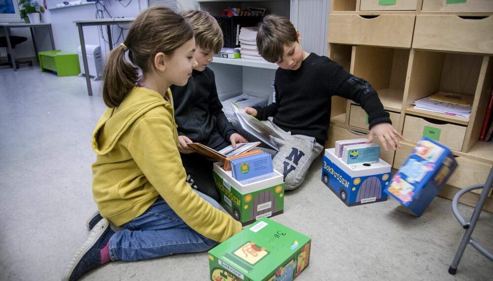 Selma, Jonas og Herman gyver løs på et par bøker gitt til skolen fra Tåsen skoles venner.