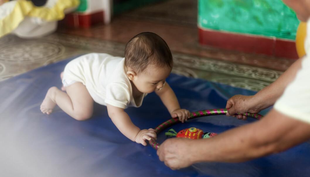 KRABBESTIMULI: Barnehagelærer Ana María Pérez legger babyen på magen og plasserer en rockering rett utenfor rekkevidde hans. Like etter er han oppe på alle fire og krabber etter ringen.