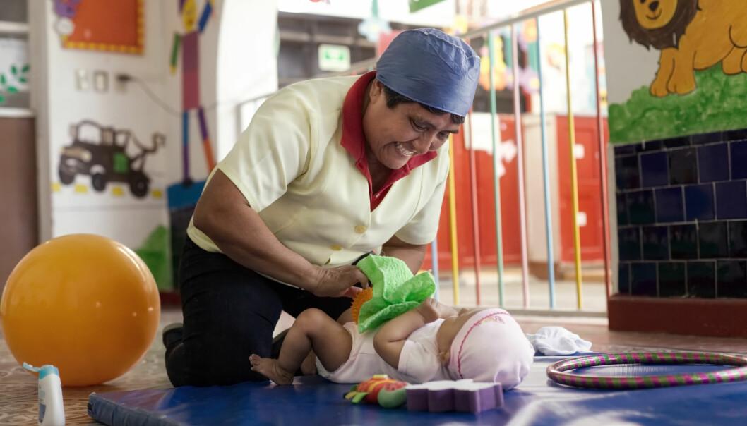 MASSASJE: Tidlig stimulering av barns utvikling er en ny satsing i mexicanske barnehager. Barnehagelærer Ana María Pérez masserer en åtte måneder gammel gutt etter å ha hatt krabbeøvelser med ham. Foto: