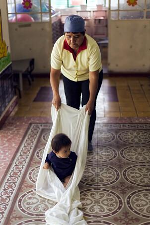 BALANSEØVELSE: Det er ikke nødvendig med dyrt materiell for å stimulere barnas utvikling, ifølge den mexicanske barnehagelæreren Ana María. Her drar hun et av barna i et stort laken for å trene balansen.