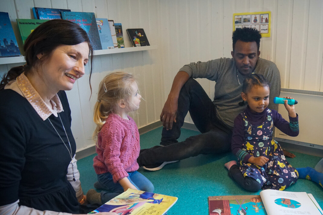 Pedagogisk leder Trine Hoftvedt og barnehageassistent  Mhreteab Weldeselassie bruker eventyr og «snakkende  penn» i språkopplæringen. Med «snakkende penn» kan barna lytte til ord og uttrykk på morsmål og norsk. Her med Pernille og Rahaf.