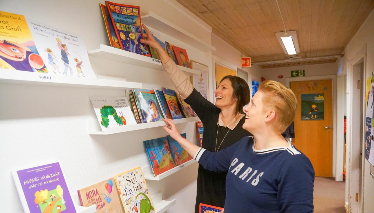 Heidi Cecilie Gilje (t.h) og Trine Hoftvedt viser fram biblioteket de har bygget opp med bøker på mange ulike morsmål. Foreldre kan låne med bøker hjem.