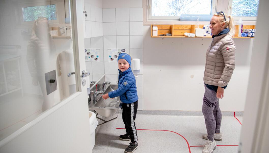 Før han kan begynne å leke, må Aksel Holst Marti vaske hender. Mamma Hanne Holst følger de oppteipede avstandsreglene.