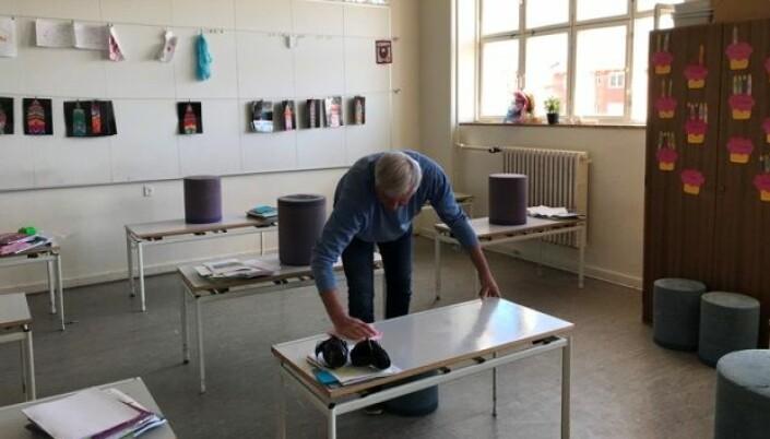 En lærer vasker av en pult.