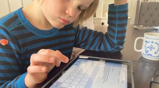 Gutt skriver p nettbrett.