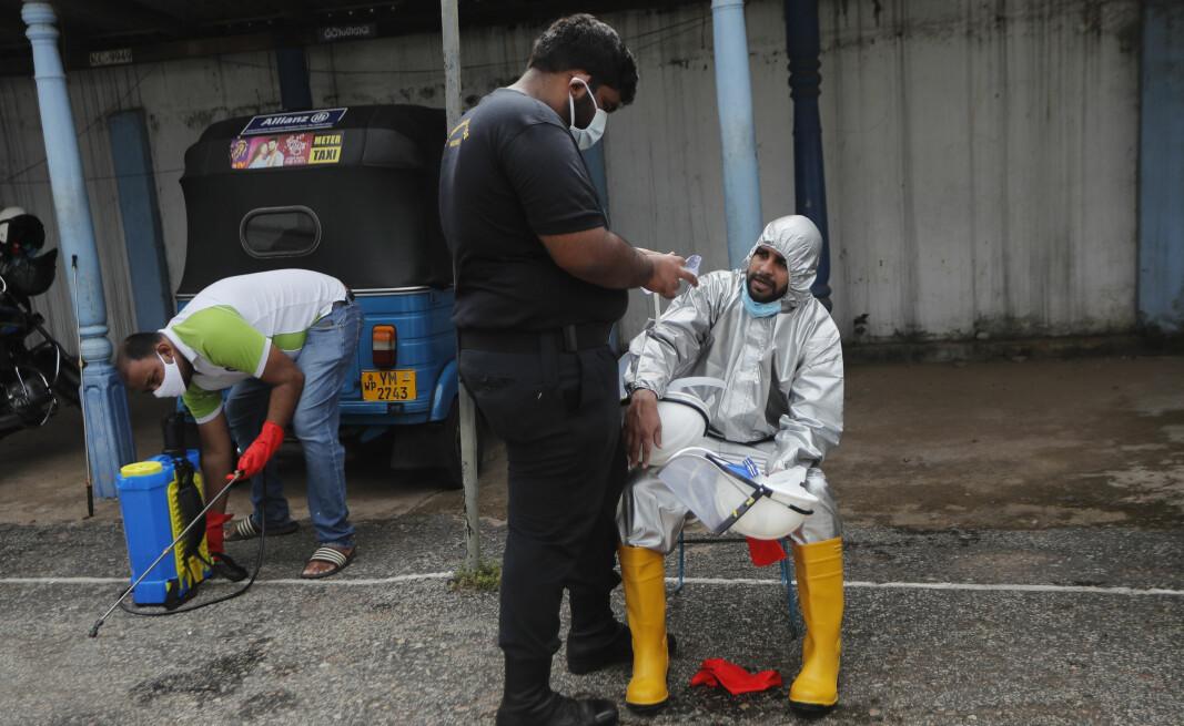 Et helsemedarbeider tar en pause i jobben med å desinfisere en skole, og får tilsyn av en kollega. Desinfisering av skoler er et tiltak som er iverksatt for å hindre spredning av korona-viruset i byen Colombo.)