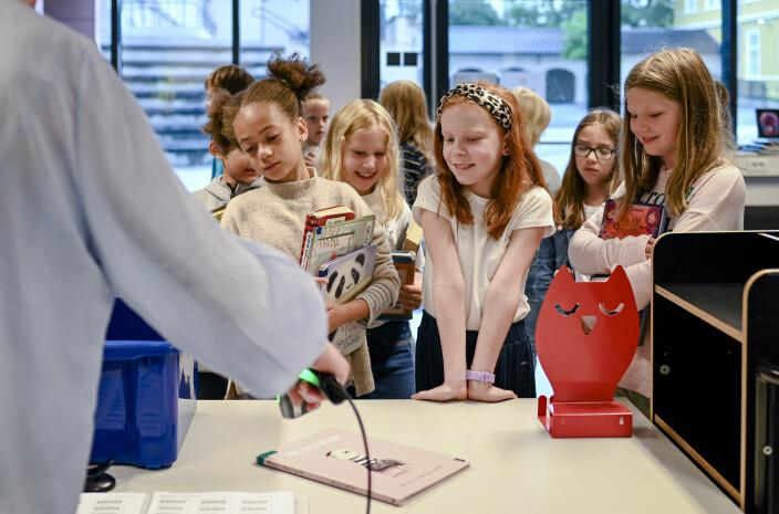 Fra venstre: Samantha Sampana Jensen,  Andrea Hoff Haslestad og Thale Ofigsbø Reistad står klare i første rekke for å låne bøker  fra skolebibliotekar Vibecke Frøyland.