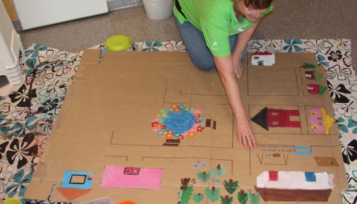 Barnehagelærer Anne Marie Dominguez viser frem bilbanen som er tegnet på baksiden av en utbrettet pappeske.