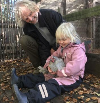Arnfinn Blichfeldt Ærø og Maria (5) gir høna Lina en liten kosestund i det fri.