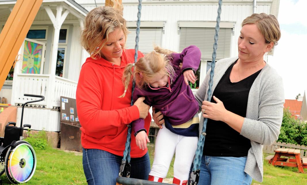 Pedagogisk leder Anita Bjørke Gulliksrud (t.v.) og styrer Anne-Gro Rojan hjelper Ellinor opp i huska. Hun begynner å bli tung, så det er godt å være to om løftene.