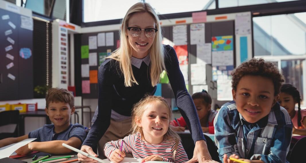 """Illustrasjonsfoto: """"Lærer hjelper elever med leksene i klasserommet"""". Copyright: AdobeStock"""