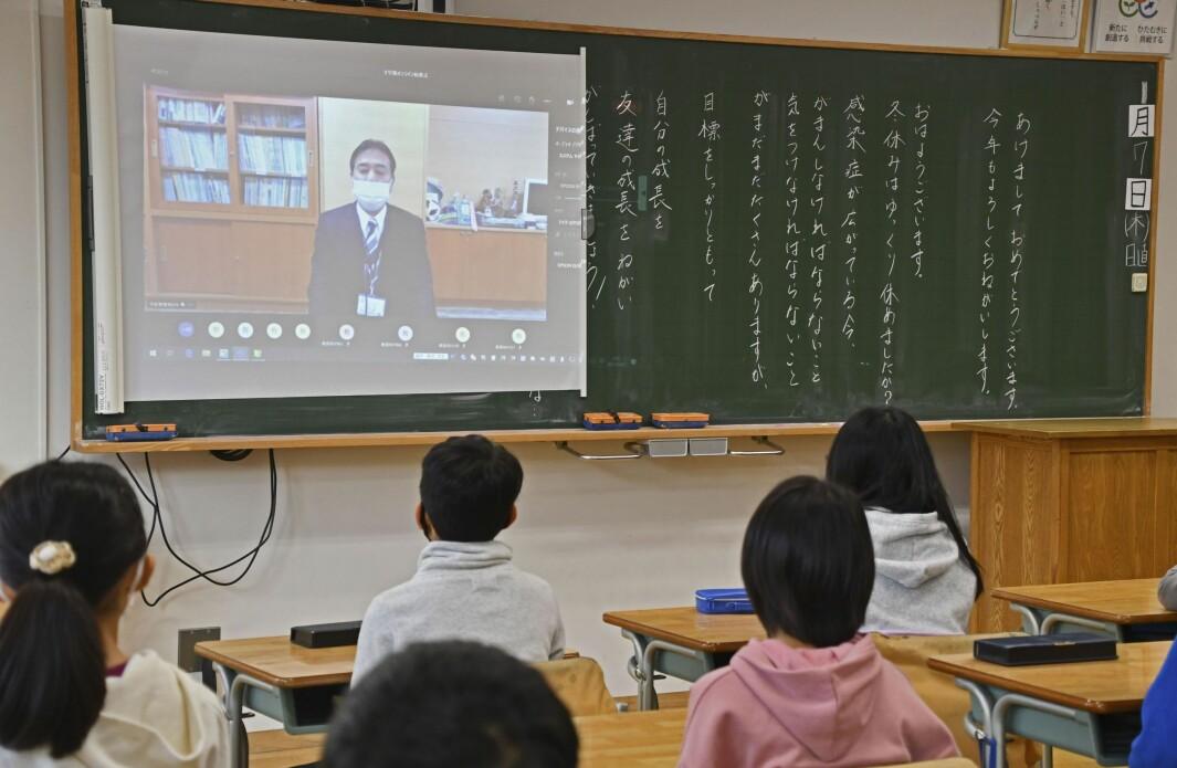 Elever ved en skole i Tokoy får med seg morgenmeldingen fra rektoren ved skolen ved skolestart torsdag 7. januar. Den japanske hovedstaden stenges ned, men skolene holdes åpne.