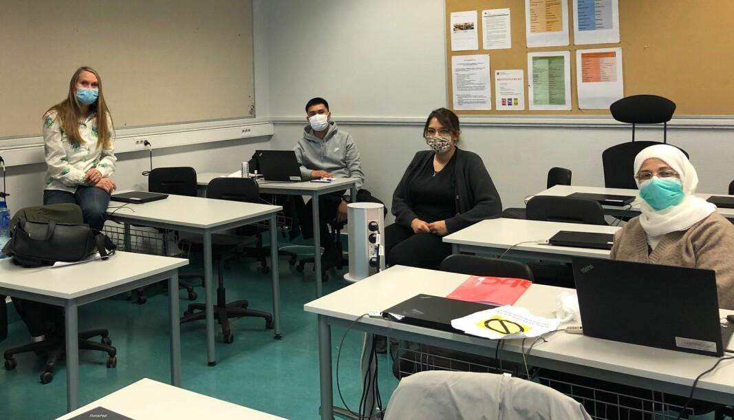 Lærer Unni Lervik sammen med deltakere ved voksenopplæringen på Sinsen. Lærerne ved skolen utstyres med munnbind og visir.