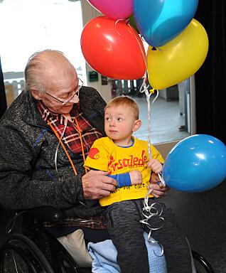 Svelvik sykehjem har gode erfaringer med å ha barnehager på besøk før koronatiden. Liam har krøpet opp i fanget til Robert Sørensen, og de koser seg begge to.