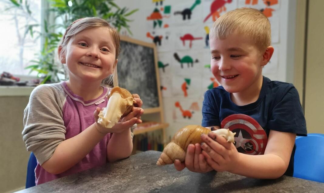 Emilia (5 1/2 år) og Matheo (6 år) viser frem to av de fire afrikanske kjempesneglene som bor på avdelingen.