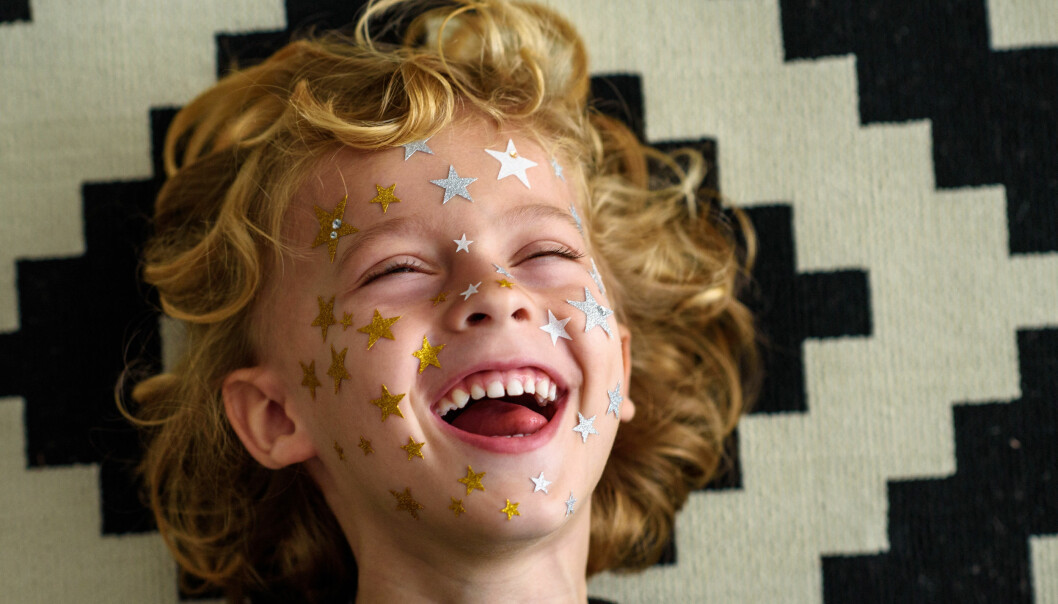 A cute young boy with curly hair laughing while having star-shaped stickers on his face