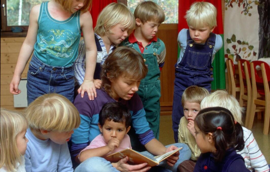 Barnehagebarn som blir lest for inne.