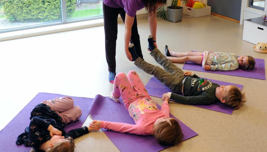 Yoga brukes som en lek der barna får oppleve hva kroppen kan få til. Både barnehageassistent og yogalærer Aleksandra Ostrowska og barna viser etter tur stillinger som de andre skal forsøke å herme etter.