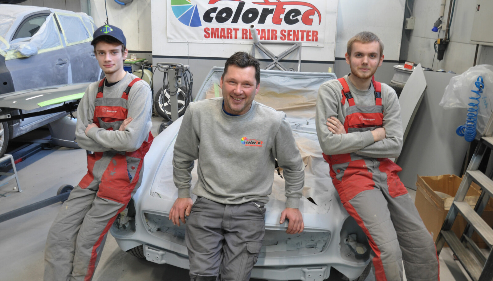 Pål Møklegård i billakkeringsfirmaet Colortec i Fredrikstad er godt fornøyd med lærlingene han har fått via Erasmus+. Til venstre Raner Ruusalep (20) og på høyre side Markus Notta (18).
