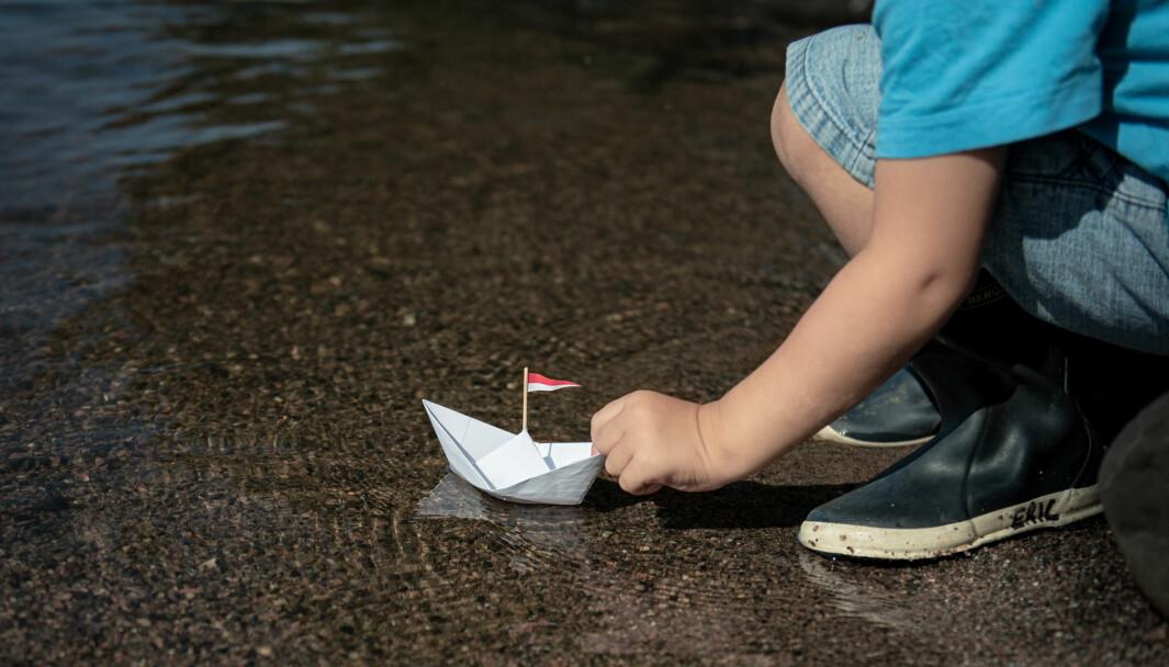 Kleiner Junge setzt Papierschiff ins Wasser
