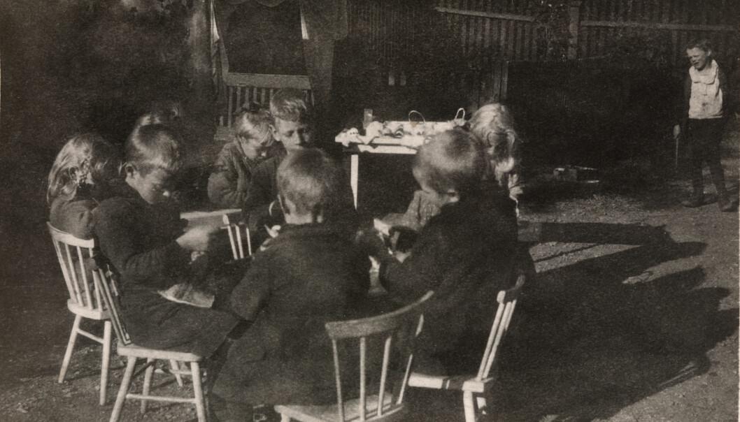 Barna i Rodeløkken Barneasyl i Oslo jobber på gårdsplassen utenfor barneasylet i 1920. Barna i barneasylene spant, vevde og strikket og bidro på denne måten til økonomien i asylene.