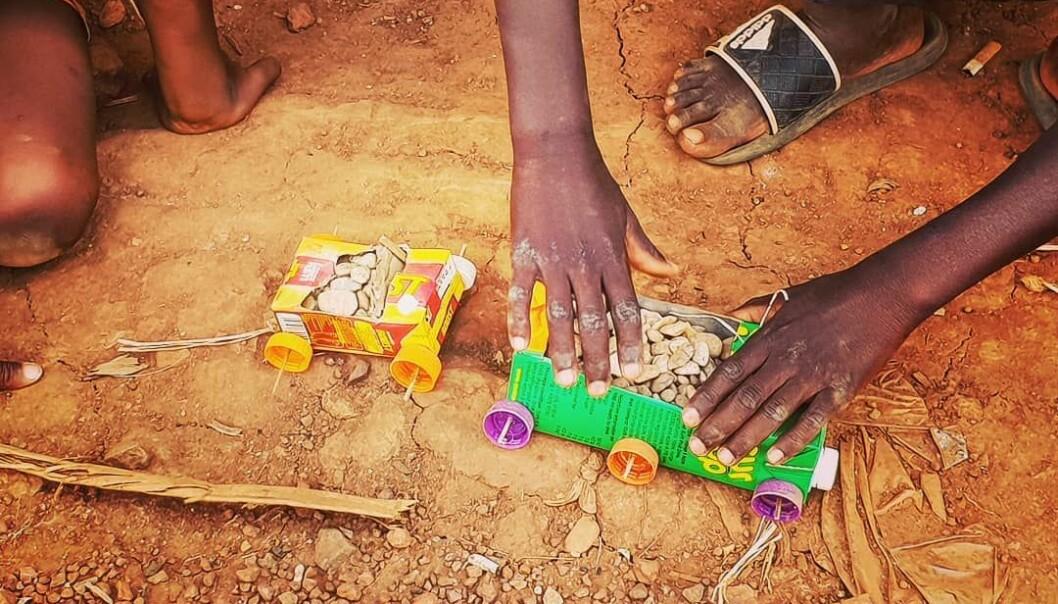 Barna leker i gatene med sand og biler. Leken er den samme enten det er i Norge eller i Uganda.