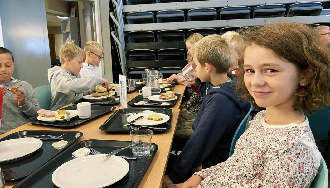 Maiken i klasse 4 c seier at det er gøy å eta lunsj saman med heile klassa rundt bordet.
