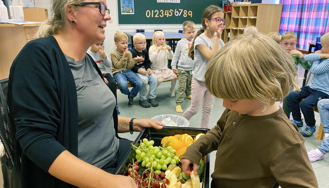 Utdeling av frukt står på timeplanen kvar dag saman med fri leik. Henry i klasse 1 a får velja av fruktfatet som Ingunn Grinde held fram.