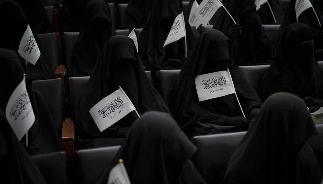 Women wave Taliban flags as they sit inside an auditorium at Kabul University's education center during a demonstration in support of the Taliban government in Kabul, Afghanistan, Saturday, Sept. 11, 2021. (AP Photo/Felipe Dana)