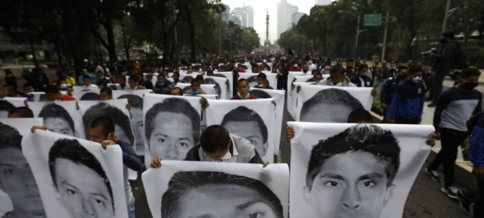 Normal college students holding images of the 43 missing students from the Rural Normal School of Ayotzinapa join family members in a march to mark the sixth anniversary of the 43 students' enforced disappearance, in Mexico City, Saturday, Sept. 26, 2020. (AP Photo/Rebecca Blackwell)