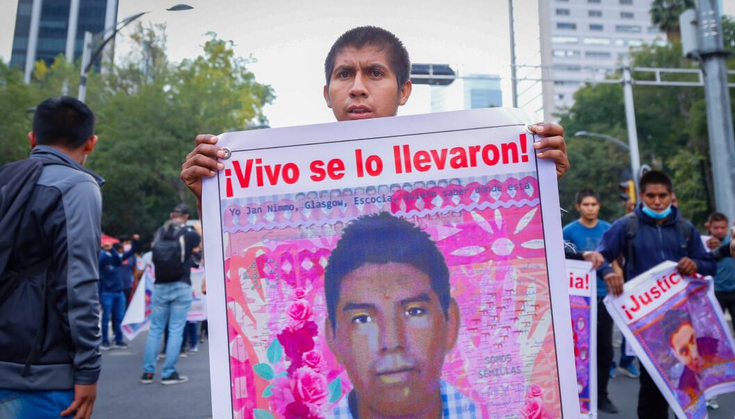 En demonstrant holder opp et bilde av en av lærerstudentene som forsvant for sju år siden.