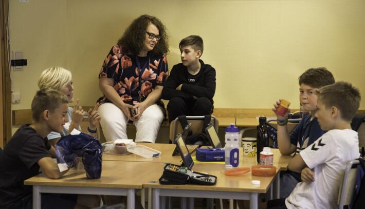 I matpausen er det tid til en liten prat. Gro har satt seg på pulten sammen med Dayan Ali. De andre elevene er fra venstre: Kai Molin Rosnes, Xander Baasland Tangen, Leon Halsnes-Noonan og Sebastian Hauger.